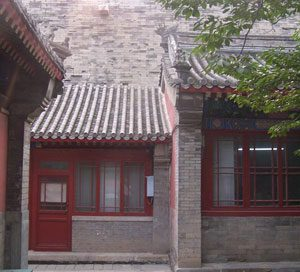 Cheng-Huang temple: a small red building between other buildings with a tile roof