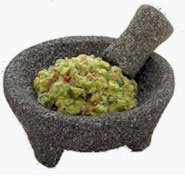 Avocados mashed into guacamole in a basalt mortar and pestle