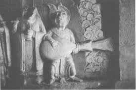 Stone carving of a person holding a big round thing with a wide neck. Flame is shooting out the end, and there is a round indentation.