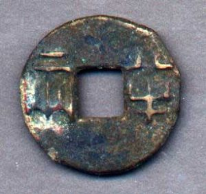 Circular metal coin with a square hole in the middle and Chinese writing on it - Ancient China trade