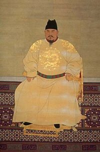 Chinese man rather overweight sitting on a chair in a long yellow silk robe