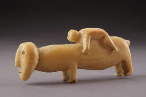 Inuit walrus ivory carving of a boy lying on the back of an animal
