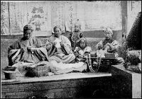A k'ang bed in an old photo, with women sitting cross-legged on it