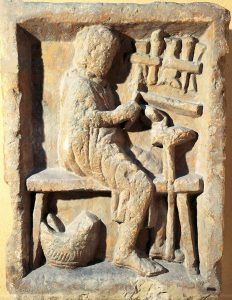 Roman stone carving of a man sitting at a bench working with tools