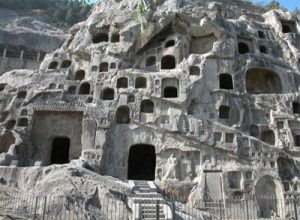 Rooms carved into the side of a big gray cliff, with stairs and walkways