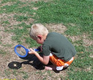 a white boy squats on grass with a magnifying glass