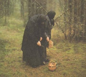 Older women wearing black dresses and head coverings with a basket on the ground in the woods