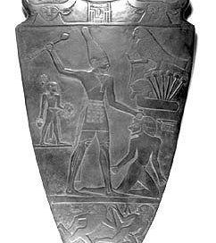 Narmer Palette: a slate stone with a carved man beating up his enemy