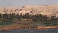 Nile river with dry cliffs in the distance