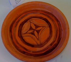 red clay plate with black designs on it