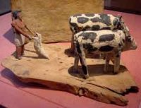 Wooden model of an Egyptian man plowing with two oxen