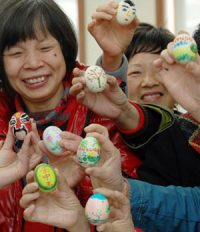 Chinese people holding painted eggs