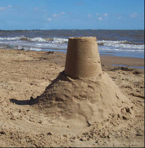 sand castle made by overturning a pail full of wet sand