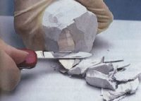 white male hands cutting a block of white stuff with a knife