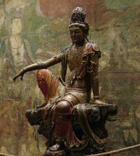 Kuan Yin statue of a woman sitting with one knee up and her arm resting on her knee