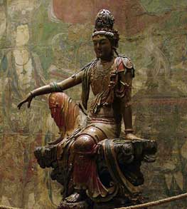Kuan Yin statue of a woman sitting with one knee up and her arm resting on her knee: Chinese gods