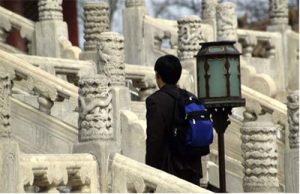 A Chinese man walking up a fancy carved white stone staircase
