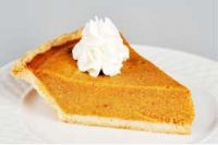 A slice of sweet potato pie: orange, with a dollop of whipped cream on top