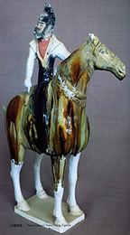 clay model in green and brown glaze of a T'ang Dynasty man on horseback