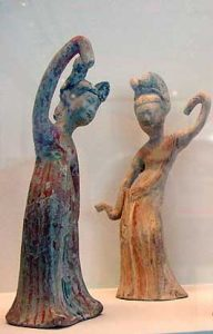 clay statues of two women dancing with very long sleeves hanging over their hands