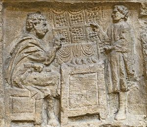 Roman stone carving of a tax collector calculating someone's taxes on an abacus
