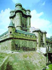 Castle of Vincennes, a tall white stone tower surrounded by lower walls and towers with a big gatehouse and moat