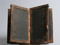 A Roman wax tablet with a wooden frame and black wax