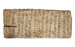 A brown rectangle of papyrus with vertical lines of black hieroglyphs on it and red marks. Egyptian schools used this sort of thing as an assignment.
