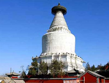 A tall white cylindrical building with a pointed top