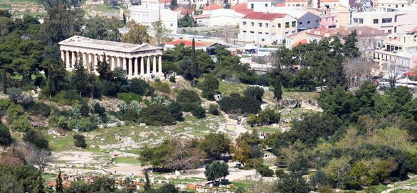 ruins with a big temple and modern Athens in the background