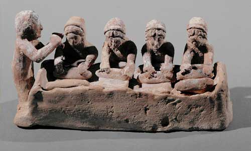a clay model of four women kneading bread and a flute player