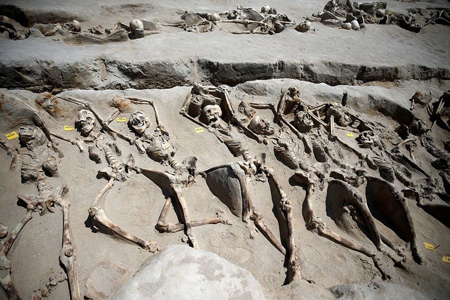 rows of skeletons with their hands tied lying on dirt