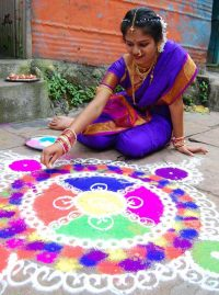 An Indian woman in a sari creates a pattern with colored sand for Diwali