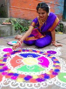 An Indian woman in a sari creates a pattern with colored rice powder for Diwali