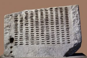 A slab of white stone with eleven columns of little slits carved into it.