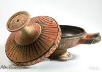 A clay bowl with a lid