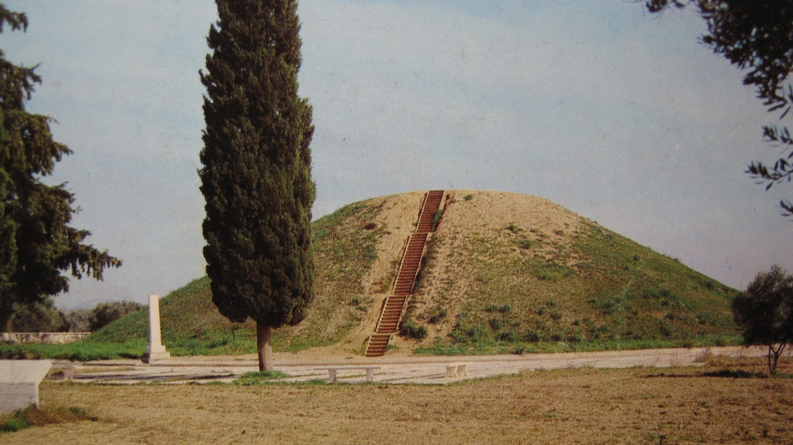 A large mound of earth in a flat field: the burial mound for the Athenians who died at the Battle of Marathon