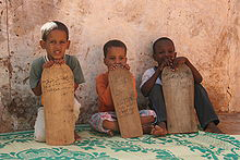 Boys in Mauretania learning Quran verses from wooden tablets