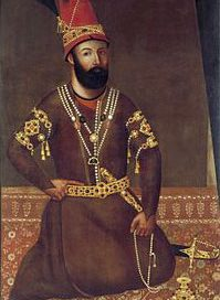 Nader Shah: a white man with a long black beard in robes with gold accessories