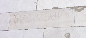 A Roman inscription turned upside down and used in the wall of Pisa's cathedral