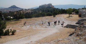 A gently sloping brown flat area on top of a hill, with evergreen trees around it - Athenian democracy