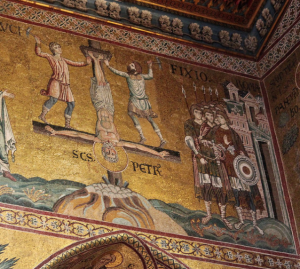 a mosaic wall with a gold background shows a man hanging on an upside down cross with his feet up. Roman officials stand around.