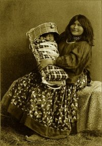 An Apache woman holding a baby in a cradleboard