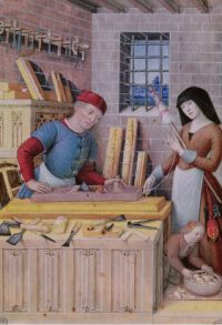 A medieval carpenter works in his shop.