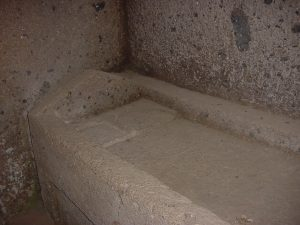 A stone bed with a stone pillow in an Etruscan cemetery-house at Cerveteri. About 500 BC