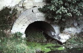 A white stone arch half full of water
