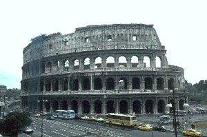 A big stone building with arches, halfway fallen down - Roman colosseum