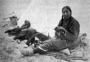 A Crow woman embroidering beads on to clothing (late 1800s)