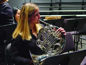 A white woman playing a French horn
