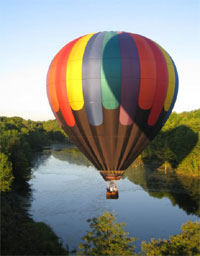Hot air balloon floating over a river - hot air rising is what causes wind